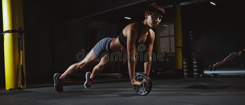 Geschiktheidsmeisje die crossfit oefeningen in gymnastiek met wiel in dark doen royalty-vrije stock foto's
