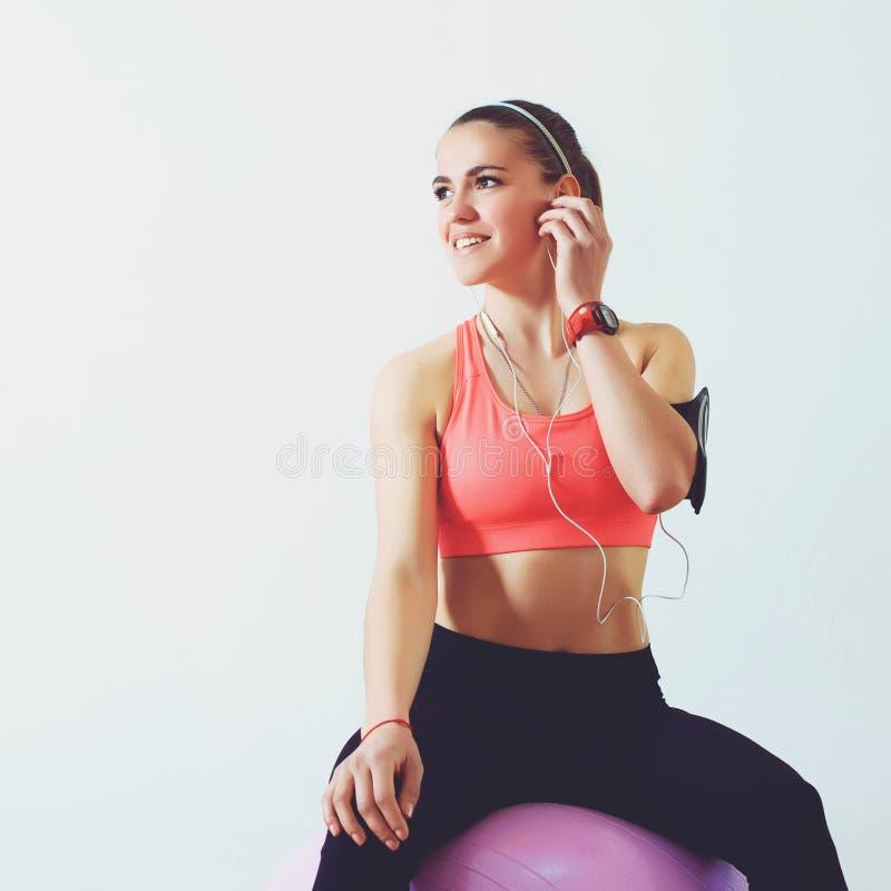 Geschiktheidsmeisje die na gymnastiektraining rusten Fitness, sport, opleiding en levensstijl concept Sportieve vrouw die smartph stock afbeeldingen
