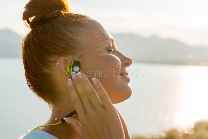 Geschiktheidsmeisje met draadloze hoofdtelefoons royalty-vrije stock afbeelding