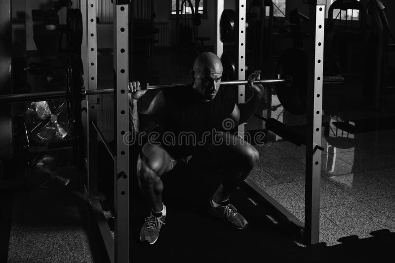Geschiktheidsmens die Barbell gebruiken die Benen binnen Gymnastiek uitoefenen royalty-vrije stock fotografie