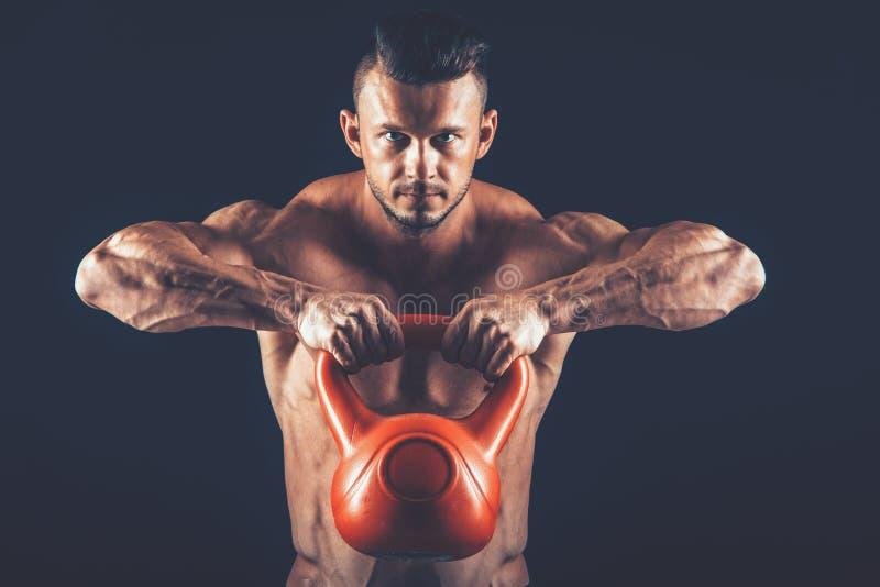 Geschiktheidsmens die een gewichtheffen doen door zware kettlebell op te heffen stock foto