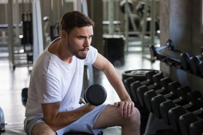 geschiktheidsmens die oefeningen doen die met gewichtheffendomoren zitten in gymnastiek sport jonge mannelijke opleiding werk gez stock afbeelding