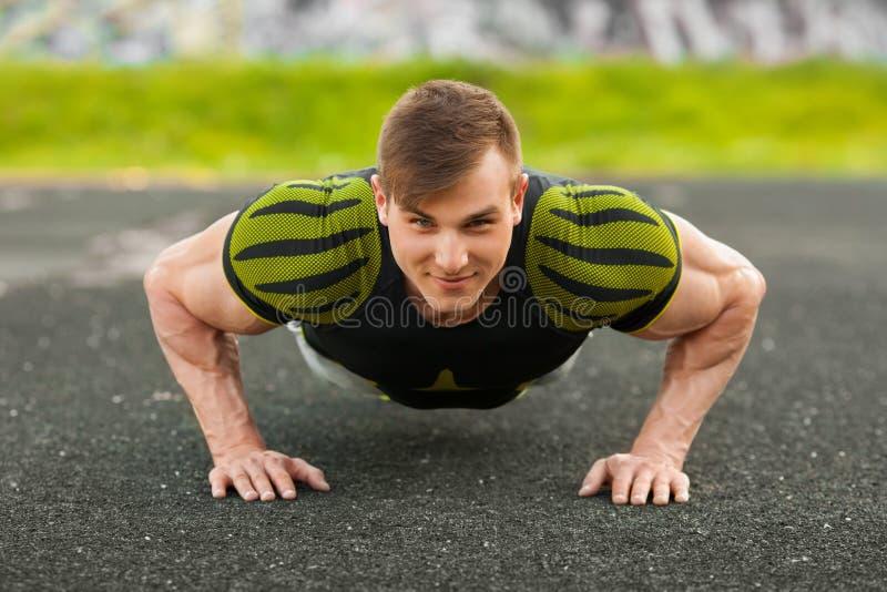 Geschiktheidsmens die opdrukoefeningen in het stadion doen, dwars opleidingstraining Sportieve mannelijke buiten opleiding stock foto's
