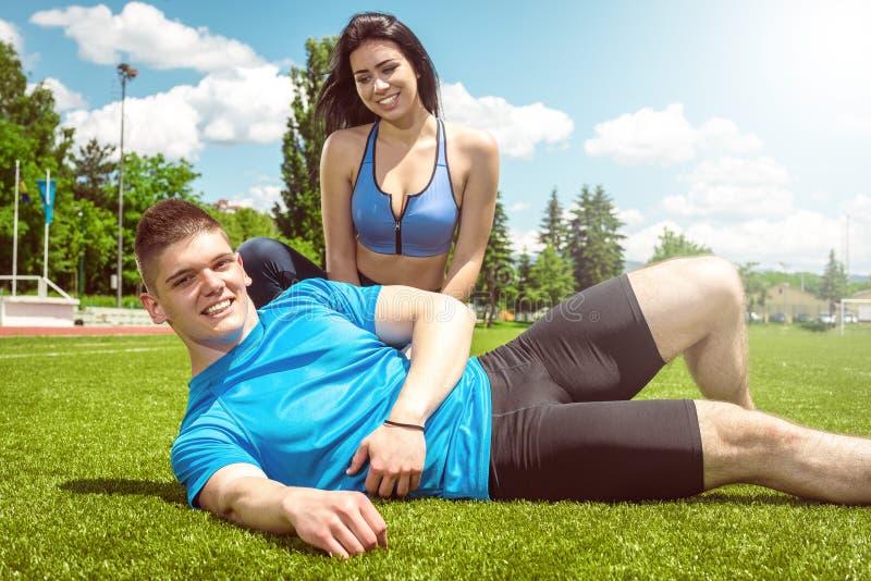 Geschiktheidspaar het ontspannen na opleiding op gras royalty-vrije stock afbeelding