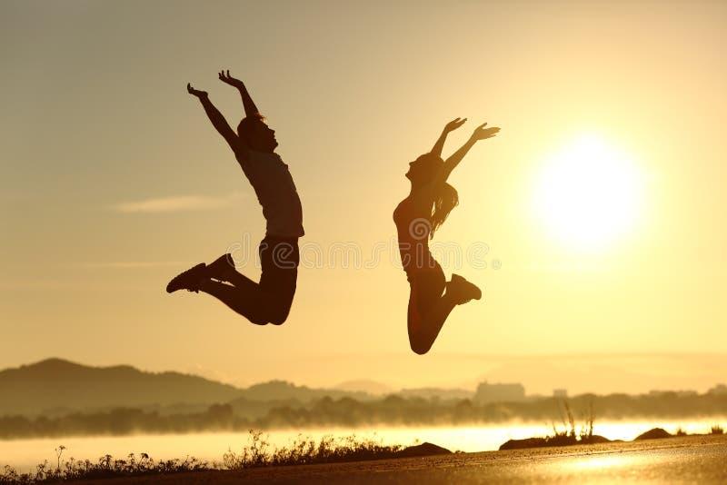 Geschiktheidspaar springen gelukkig bij zonsondergang stock foto