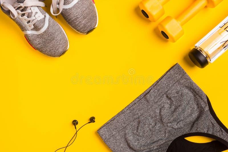 Geschiktheidstoebehoren op een gele achtergrond Tennisschoenen, fles water, hoofdtelefoons en sportbovenkant royalty-vrije stock afbeeldingen