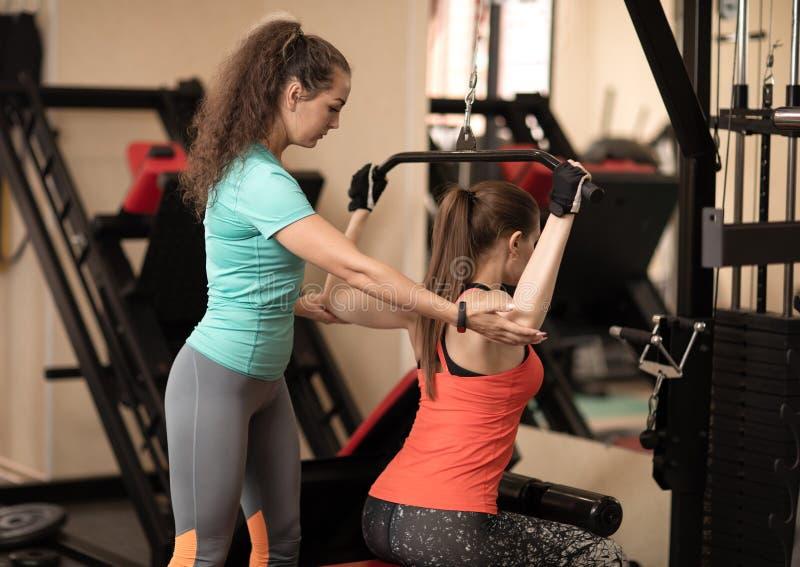 Geschiktheidstrainer die jonge vrouw met oefening bijstaan in gymnastiek royalty-vrije stock afbeelding