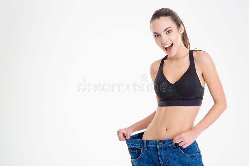 Geschiktheidsvrouw aantonen die dat de jeans voor haar te groot werden royalty-vrije stock afbeelding
