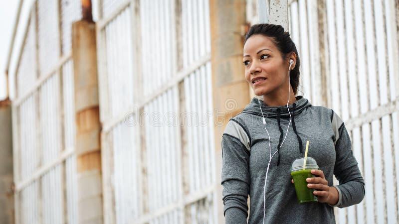 Geschiktheidsvrouw die detox smoothie op trainingrust drinken stock afbeelding