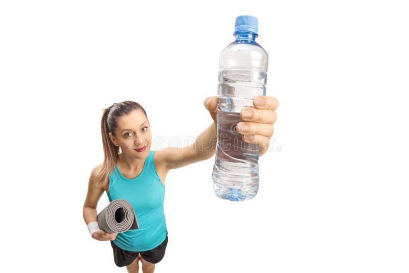 Geschiktheidsvrouw die een oefeningsmat en een fles water houden stock afbeeldingen