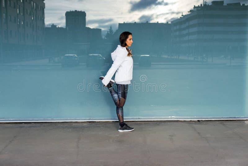 Geschiktheidsvrouw die en zich in de stad uitrekken uitoefenen royalty-vrije stock afbeelding