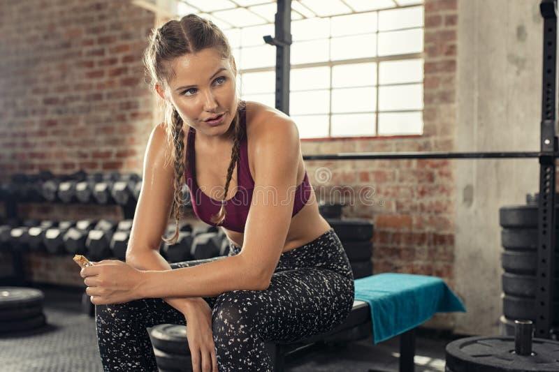 Geschiktheidsvrouw die energiebar eten bij gymnastiek royalty-vrije stock afbeelding
