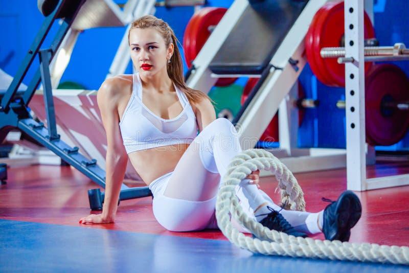 Geschiktheidsvrouw die met slagkabel bij gymnastiek uitwerken Rust op de vloer stock fotografie