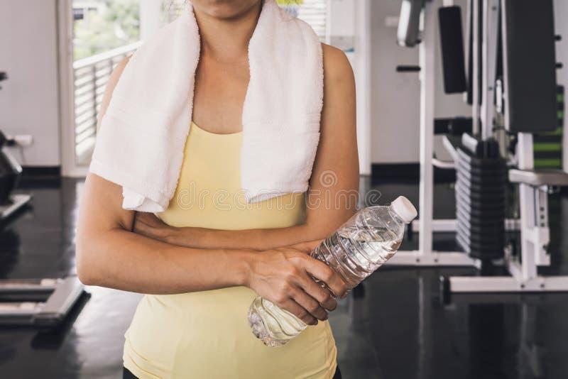 Geschiktheidsvrouw die met witte handdoek een fles water houden stock foto