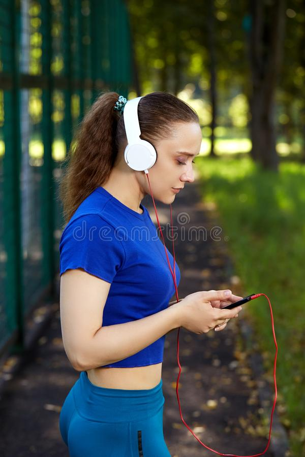 Geschiktheidsvrouw die na het intense fysieke opleiding listerning aan muziek rusten royalty-vrije stock fotografie