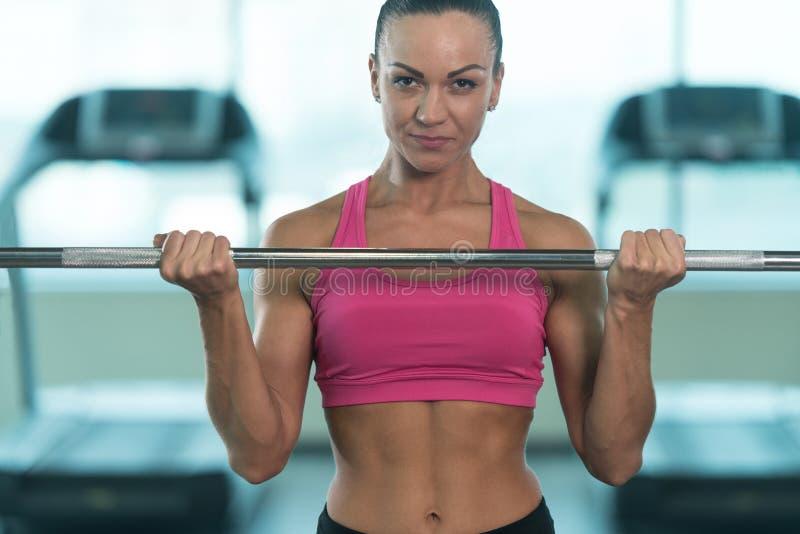 Geschiktheidsvrouw die Oefening voor Bicepsen met Barbell doen royalty-vrije stock foto