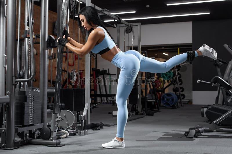 Geschiktheidsvrouw die oefening voor glutes, kabelterugslag doen Atletische meisjestraining bij de gymnastiek Mooi uiteinde in be stock foto's