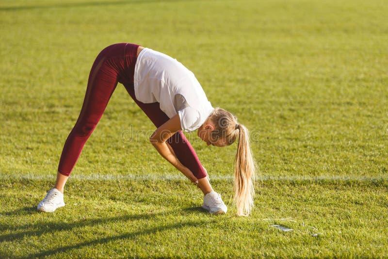 Geschiktheidsvrouw die Oefeningen doen bij het Voetbalstadion stock afbeeldingen