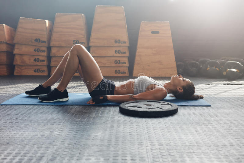 Geschiktheidsvrouw die op haar terug na een gymnastiektraining liggen stock foto's