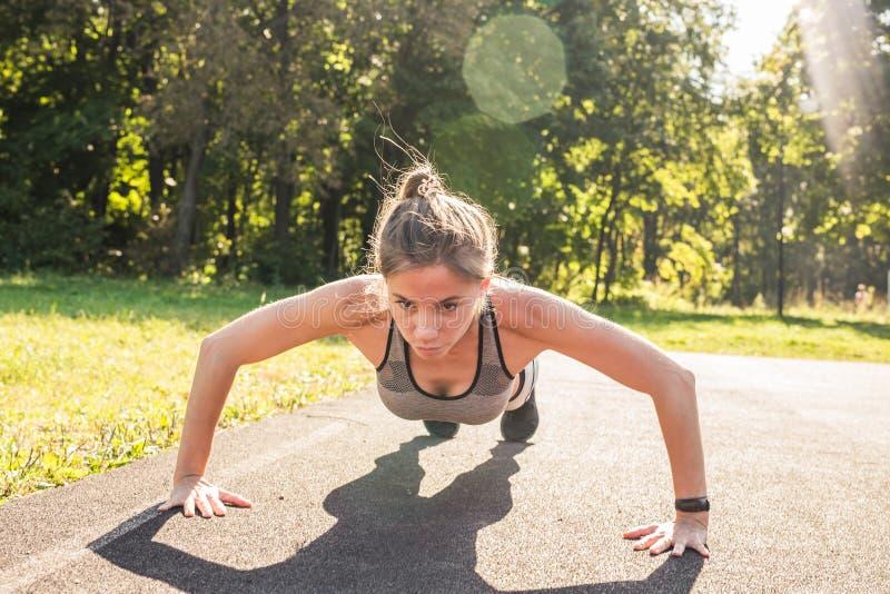 Geschiktheidsvrouw die opdrukoefeningen doen tijdens openlucht dwars opleidingstraining Mooie jonge en geschikte fitness sport mo stock afbeeldingen