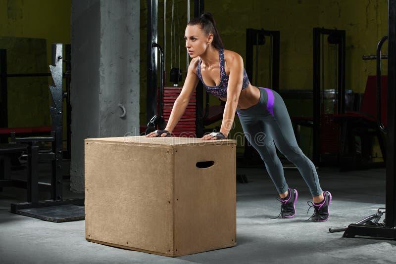 Geschiktheidsvrouw die opdrukoefeningen op crossfitdoos doen in gymnastiek Atletische meisjestraining stock afbeelding