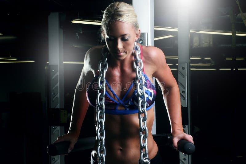 Geschiktheidsvrouw die tricepsoefeningen in de gymnastiek met een metaalketting doen royalty-vrije stock fotografie
