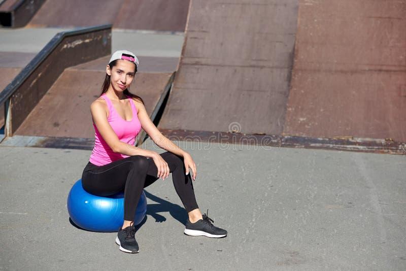 Geschiktheidsvrouw die uitrekkende oefeningen met geschikte bal op stedelijke stadsachtergrond doen royalty-vrije stock afbeelding