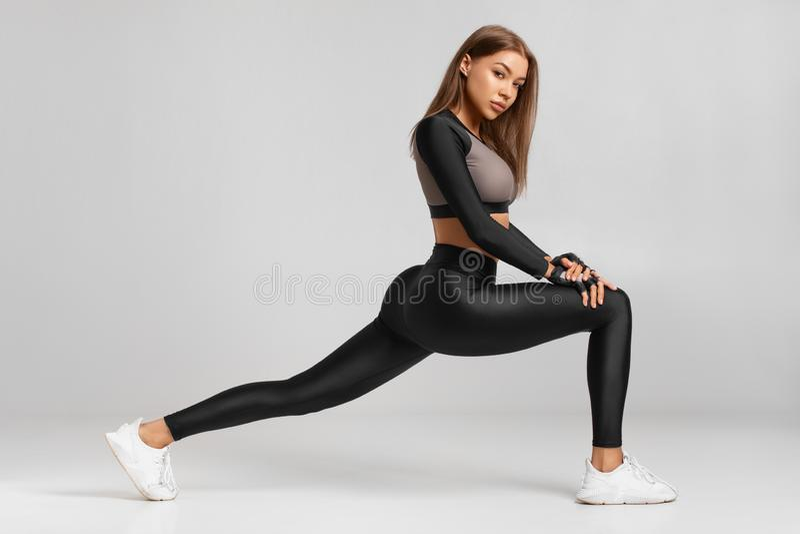 Geschiktheidsvrouw het doen valt oefeningen voor de training van de beenspier opleiding uit Het actieve meisje die voor één beens stock fotografie