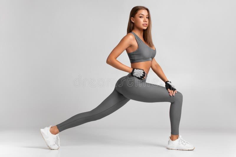 Geschiktheidsvrouw het doen valt oefeningen voor de training van de beenspier opleiding uit Het actieve meisje die voor ??n beens royalty-vrije stock afbeeldingen