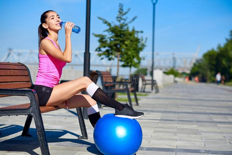 Geschiktheidsvrouw met fles en rubber geschikte bal Vrouwelijk drinkwater na opleiding op bank in de zomerpark royalty-vrije stock afbeeldingen
