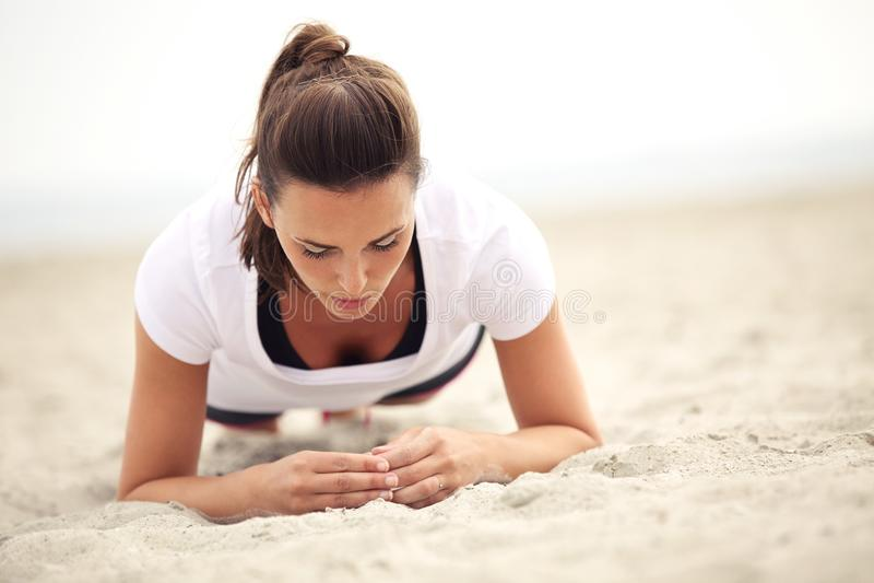 Geschiktheidsvrouw op het Strand die Kernoefeningen doen stock fotografie