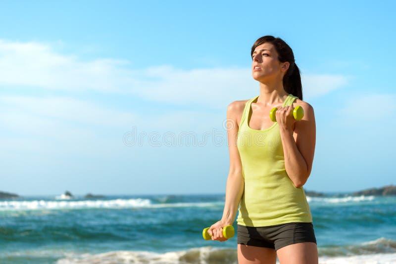 Geschiktheidsvrouw opleidingsbicepsen op strand stock foto's