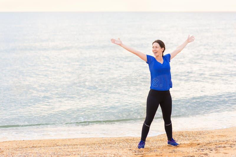 Geschiktheidsvrouw in sporstwear op het strand royalty-vrije stock fotografie
