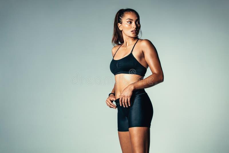 Geschiktheidsvrouw in sportkleding die zich over grijze achtergrond bevinden royalty-vrije stock afbeelding