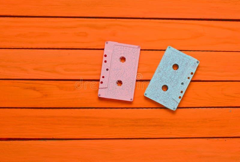 Geschilderd in een roze blauwe pastelkleur audiocassette op een oranje houten achtergrond stock afbeeldingen