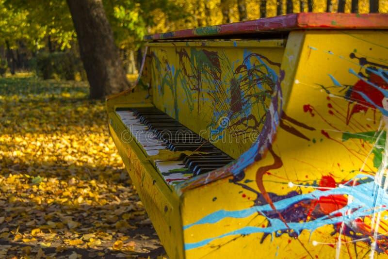 Geschilderde kleuren van de piano in een de herfstpark Het esdoornblad ligt op de sleutels royalty-vrije stock fotografie