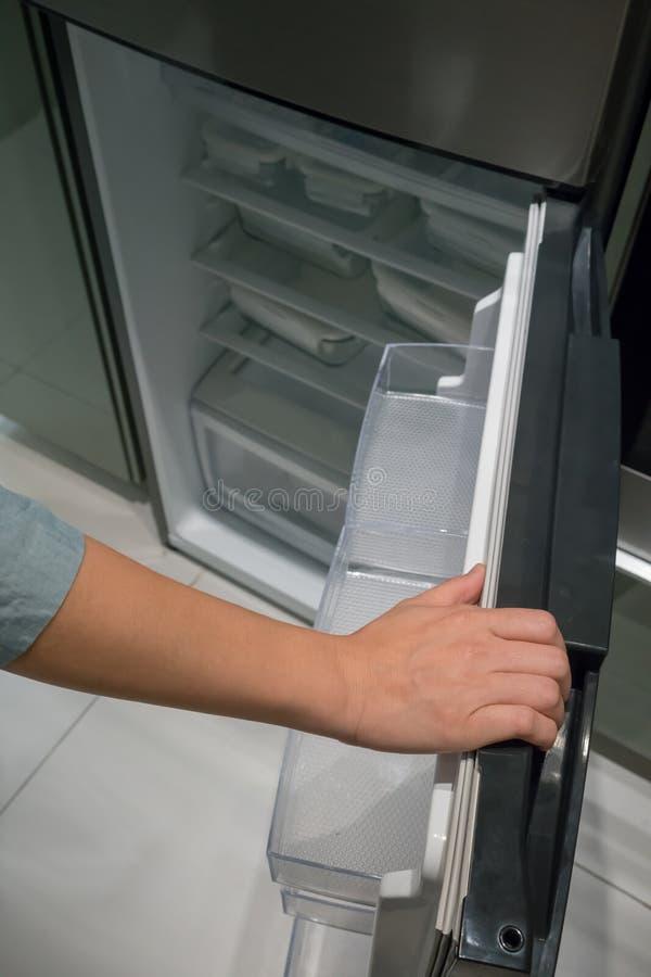 Geschlossen herauf die Hand, die den silbernen Farbgriff von Kühlschrank d öffnet stockfotos