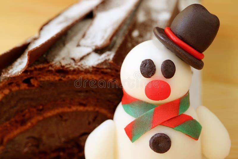 Geschlossen herauf ein entzückendes Schneemann-Marzipan mit unscharfer Schokolade Yule Log Cake im Hintergrund stockbilder