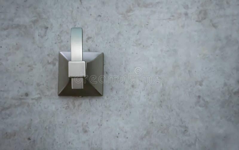 Geschlossen herauf gebürstetes Metall kleiden Sie den Haken, der an der modernen Zementwand angebracht wird stockbilder