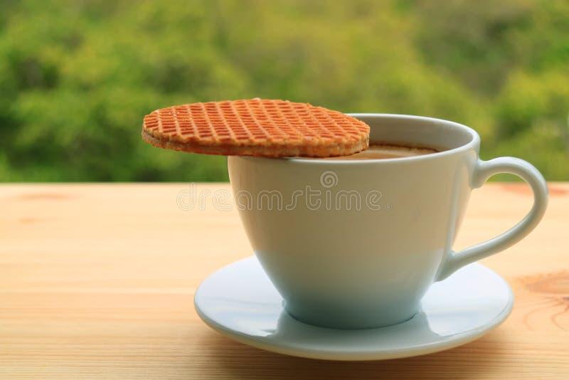 Geschlossen herauf Stroopwafel setzte auf die Schale des heißen Kaffees gedient auf Holztisch, unscharfes grünes Laub im Hintergr lizenzfreie stockfotografie