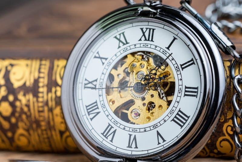 Geschlossen herauf Weinlesetaschenuhr auf Buch unter Verwendung als Zeitsymbol oder b stockfoto
