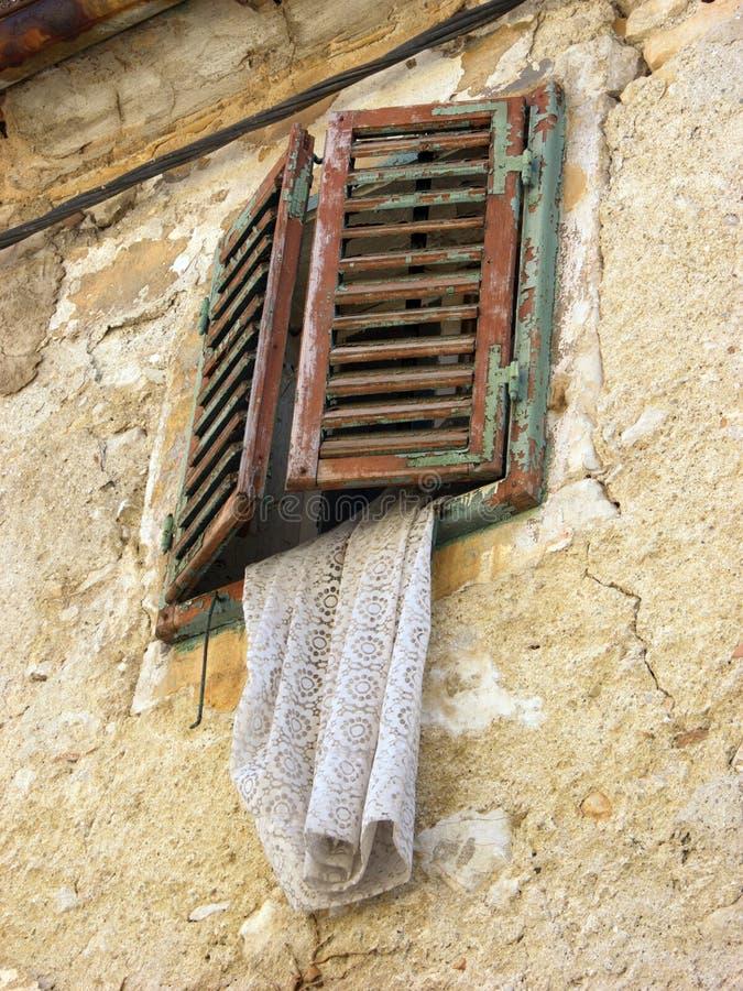 Geschlossene antike Fensterläden mit weißem antikem Vorhang auf gebrochener Fassade in Bakar, Kroatien stockfotografie