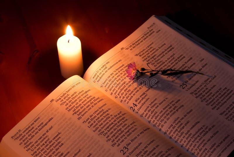 Geschlossene Bibel durch Kerzeleuchte stockfotos