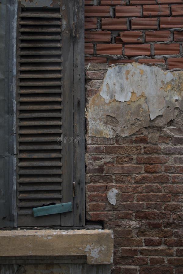 Geschlossene Jalousien auf einer verwitterten Ziegelsteinwand stockbilder