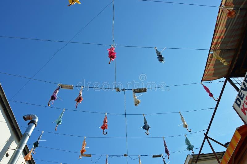 Geschlossene Regenschirme, die über der gehenden Straße hängen lizenzfreies stockfoto