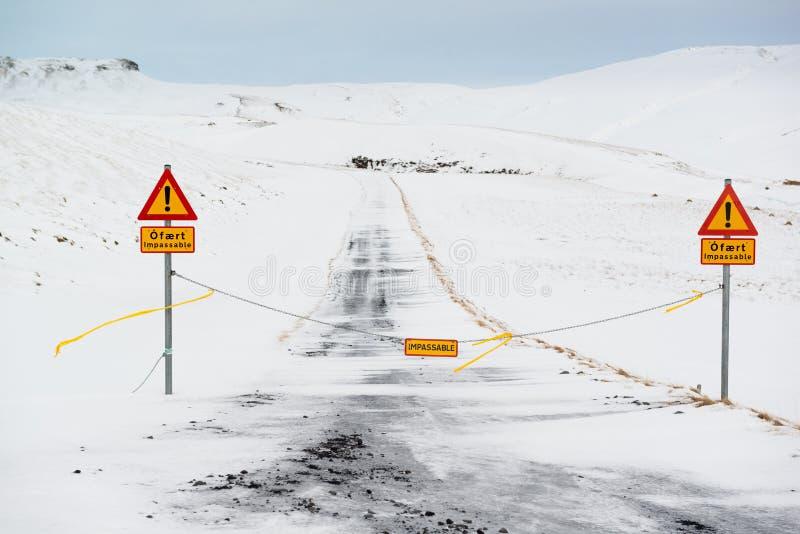 Geschlossene Straße mit Aufmerksamkeit unterzeichnet, unwegsame Schotterstraße im Winter, Island stockfoto