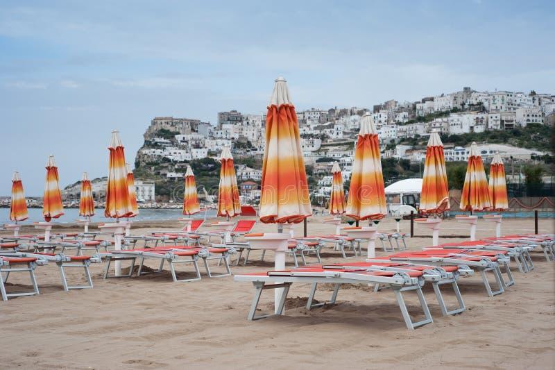 Geschlossene Strandschirme und Klappstühle auf einem leeren Strand stockbild