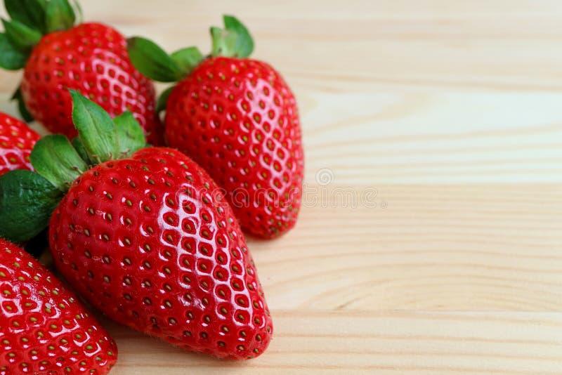 Geschlossener hoher Haufen von den vibrierenden roten frischen reifen Erdbeerfrüchten lokalisiert auf Holztisch mit freiem Raum f lizenzfreie stockfotografie