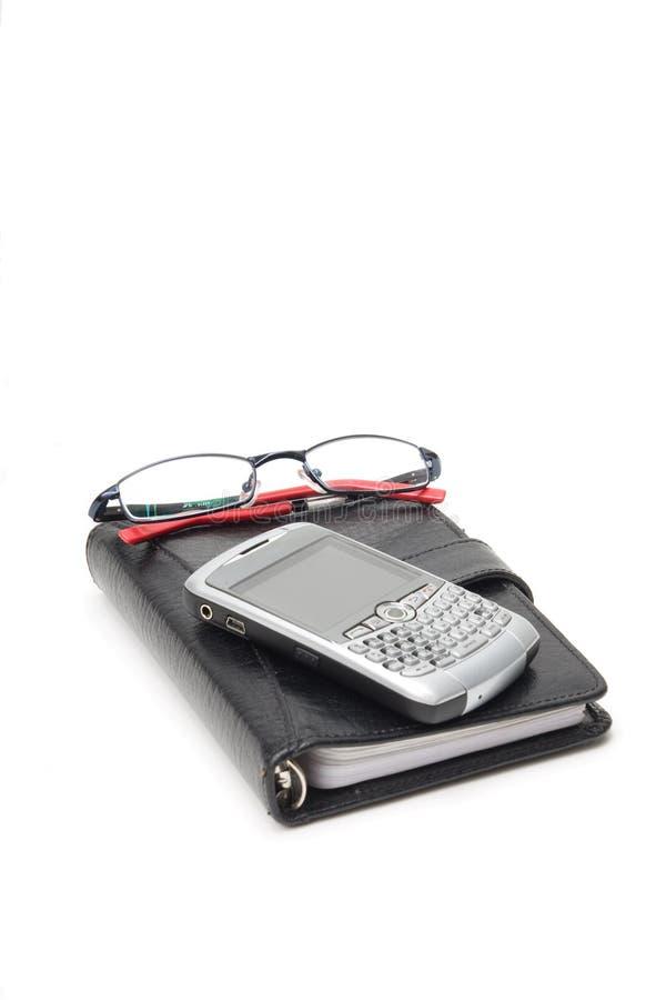 Geschlossener Planer mit Gläsern und PDA stockfotos