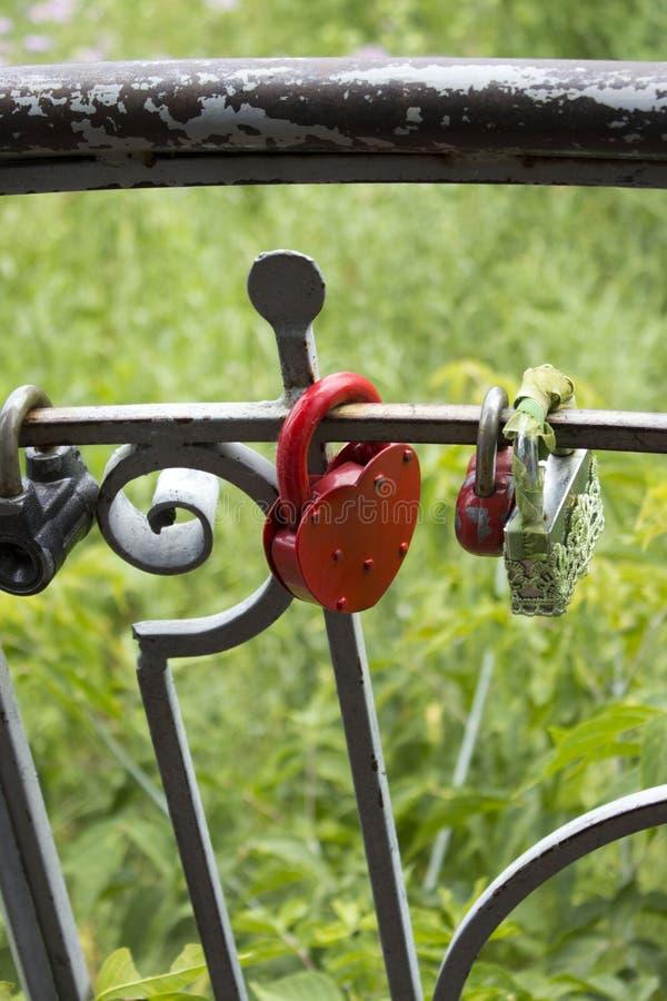 Geschlossener roter alter Verschluss, der am Zaun hängt stockfoto
